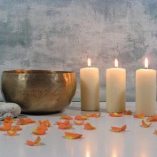 Bild von einer Klangschale 3 weissen Kerzen und Blütenblättern