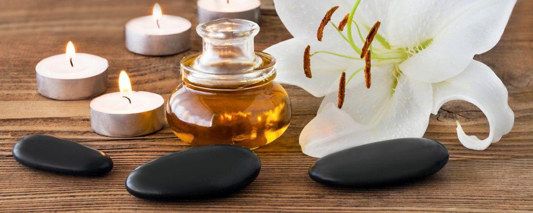 Bild von Kerzen, schwarzen Steinen und einem Glastopf mit Honig vor einer weißen Blume